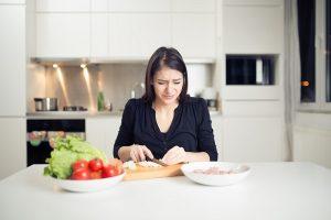 Na imagem mostra uma mulher cortando cebola e chorando.